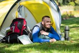 Smiling hiker lying in tent