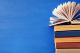 stack of old books in front of blue wooden background