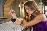 Thoughtful woman having red wine at bar counter