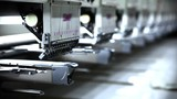 A row of industrial sewing machines used for manufacturing clothing.