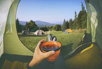 Woman lying in a tent with coffee ,view of camping with  people near the fire   and forest © natalia_maroz
