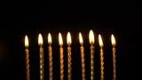 Footage golden burning candles set on black background. 4K