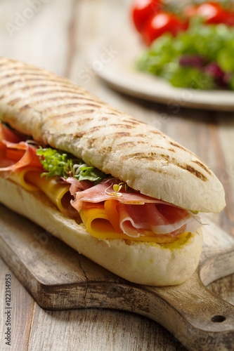 Poster Traditional Italian sandwich with ham and cheese served warm.