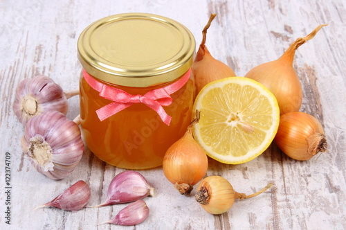 Honey in glass jar, onion, lemon and garlic, healthy nutrition and strengthening Poster