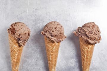 Chocolate ice cream cones are together.