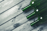 Three empty green wine bottles on black grunge wooden table background.