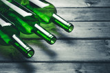 Three green wine bottles on gray grunge wooden table background.