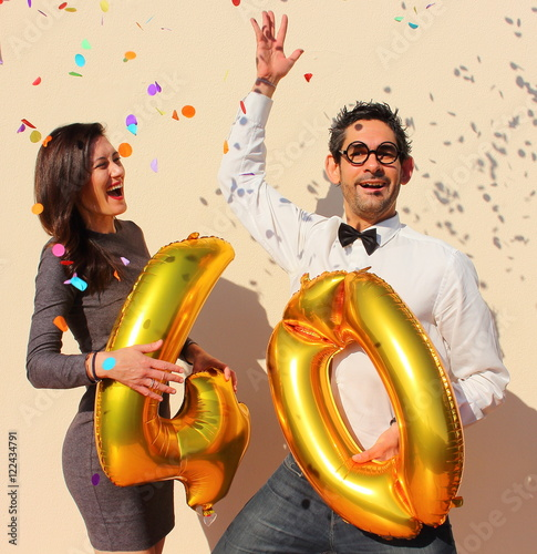 Poster Cheerful couple celebrates a forty years birthday with big golden balloons and colorful little pieces of paper in the air
