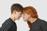 Сonflict of interest and determining family relationships - Redhead woman and teenage boy in similar t-shirts resting heads against each other on gray background - Mother and son disagreement