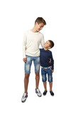Tall teenager and little boy stand together embracing and looking face to face isolated on white background