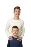Teenage boys stands behind putting hands on his little brother shoulders isolated on white background - focus on little boy face