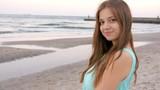 Beautiful girl stays at the beach near sea