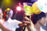 Martini glass in female hand against clubbing people