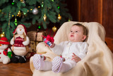 A baby in white knitted woolen costume holds gift box