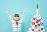 Portrait of little girl standing by Christmas tree and rejoicing
