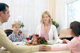 Praying family of four at thanksgiving dinner