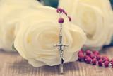 Catholic rosary and white roses