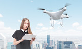 Young woman controlling a drone in big city