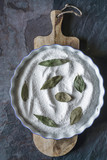 Baking dish with salt and bay leaf on the stone background vertical