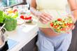 Schwangere Frau mit Babybauch isst gesunden Salat in Küche