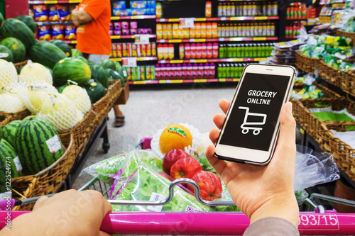 Smart phone with grocery shopping online on screen over blur supermarket background, retail business and technology concept