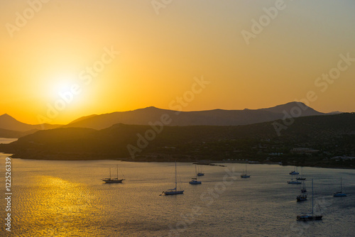 Sea lagoon with a tourist ship at sunset