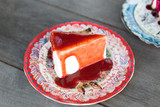 Strawberry Cheesecake on beautiful flower dish pattern with strawberry sauce on wooden table.