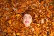 Young lady covered by leaves.