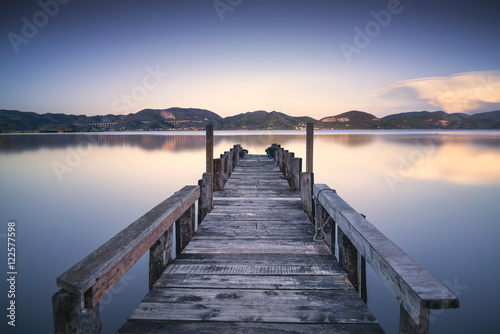 Plexiglas Pier Wooden pier or jetty on a blue lake sunset and sky reflection on