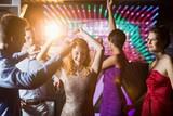 Fototapety Smiling friends dancing on dance floor