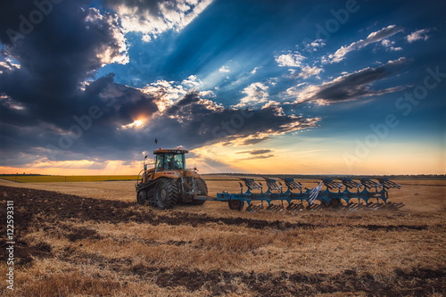 Plakát Farmer in tractor preparing land with cultivator