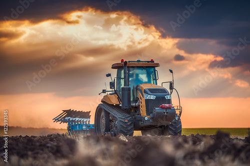 Plagát Farmer in tractor preparing land with cultivator