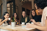 Six beautiful women drinking coffee and chatting.