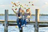 Fototapety Seniorenpaar wirft buntes Laub in die Luft, Herbsttag am See