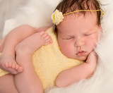 lovely baby in yellow romper sleeping with legs crossed