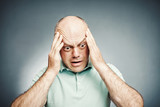 middle-aged man put his hand to his head complains, with shocked - 122610384
