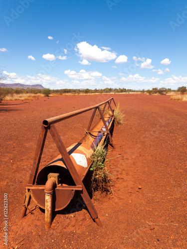 Foto op Canvas Baksteen an old rusty cattle feeder, in the harsh arid red landscape of the australian outback bush.