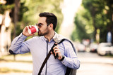 Young businessman walking outside and drinking coffee.