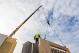 Roofer builder worker with crane installing structural Insulated Panels SIP. Building new frame energy-efficient house - 122627112