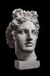 Gypsum statue of Apollo's head on a black background