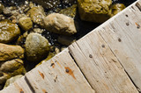 A close up of an old wooden jetty texture with rocks and sea below.