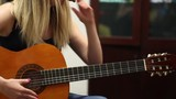 Beautiful girl adjusts guitar