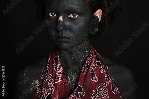 Valokuva Photo portrait of a girl in sunglasses and red dress dark gray paint on the face