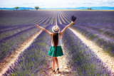 Fototapety Young woman with raised hands holding lavender bouquet standing on the lavender field in Provence