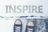 Sneakers standing over Inspire title on pavement