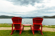Two red chairs overlooking the lake and mountains