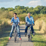 Fototapety lachende Senioren bei einer Radtour, Freude im Rentenalter