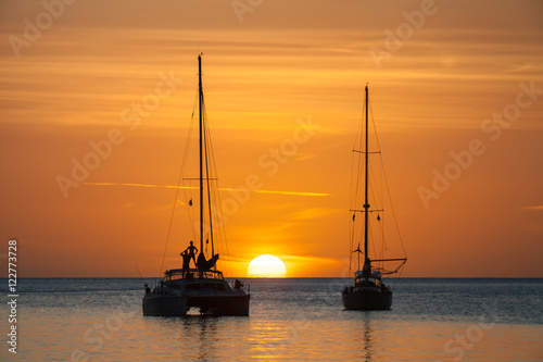 Sun setting over ocean, person standing on sailboat in silhouette Poster