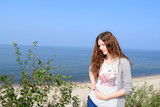 A beautiful woman stands on a height near the sea