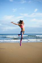 Sportowy brazylijska kobieta tańczy i skoków na plaży. Czarny szczęśliwy tancerz uprawiania skoków tańca i zabawy na świeżym powietrzu.